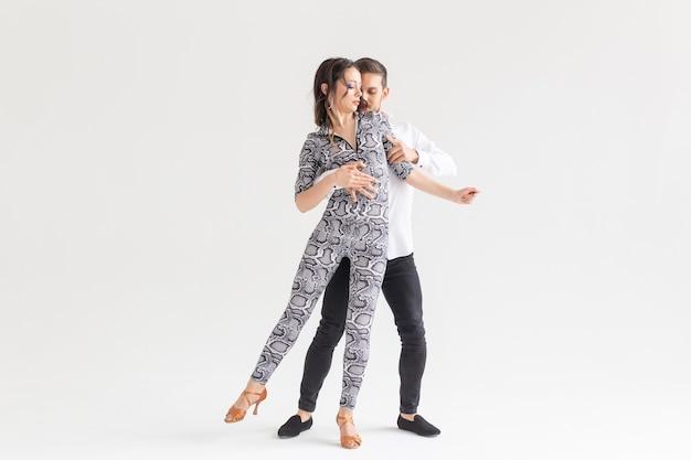 Sociale dans, kizomba, tango, salsa, mensenconcept - mooi paar die bachata op witte achtergrond met exemplaarruimte dansen