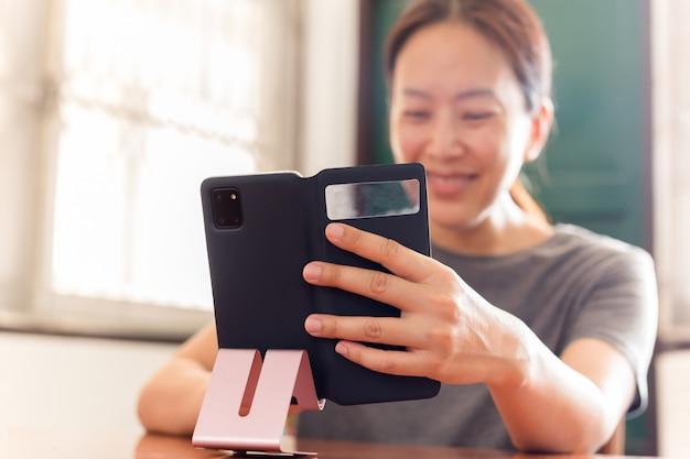 Sociale distantiëren gelukkig lachende vrouw met behulp van mobiele telefoon video-oproep vrienden en familie.