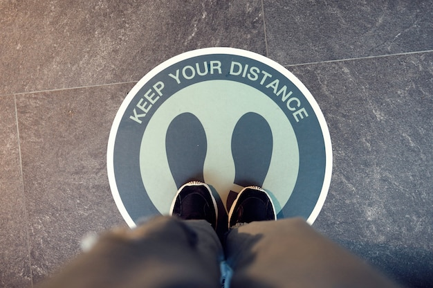 Sociale inscriptie op de vloer van de supermarkt. afstand bewaren in de openbare samenleving om covid-19 te beschermen