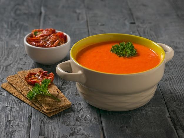 Soep fijngestampte groenten en gedroogde tomaten met brood toast op een houten tafel