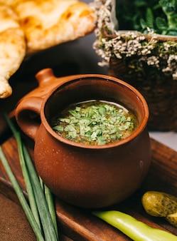 Soep in kleipot geserveerd met kruiden