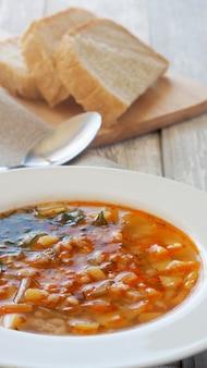 Soep met aardappelen en gerst in een witte plaat en brood op een snijplank