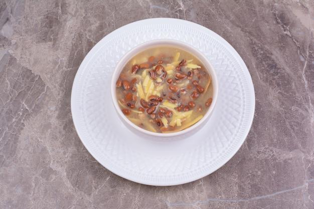 Soep met bruine bonen en spaghetties in een wit keramiek kopje