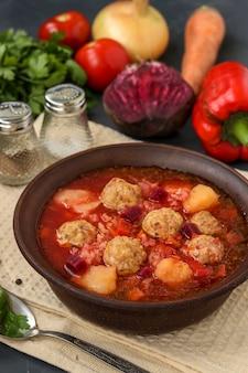 Soep met gehaktballen en groenten in een donkere kom, close-up