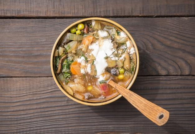 Soep met groenten en zure room in een diep bord op het oppervlak van de donkere planken. bovenaanzicht.