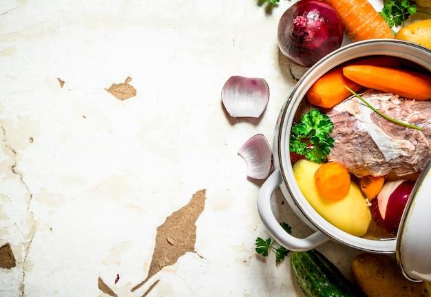 Soep met groenten, varkensvlees, kruiden en specerijen in een pan.