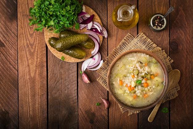 Soep met ingelegde komkommers en parelgort - rassolnik op een houten achtergrond. bovenaanzicht.