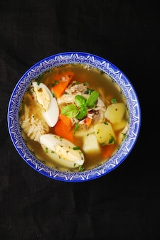 Soep met kip en groenten in kom op donkere tafelbladweergave.