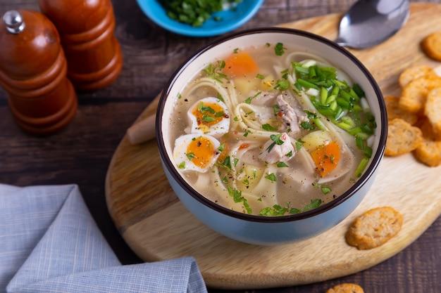 Soep met kip, noedels, aardappelen, kwarteleitjes en wortelen