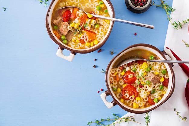 Soep met kleine pasta, groenten en stukjes vlees in kom op blauwe tafel. italiaans eten. bovenaanzicht. plat liggen