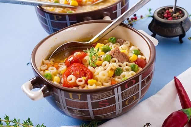 Soep met kleine pasta, groenten en stukjes vlees in kom op blauwe tafel. italiaans eten.
