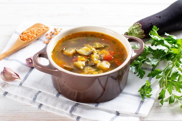Soep met linzen en groenten op een lichte tafel.