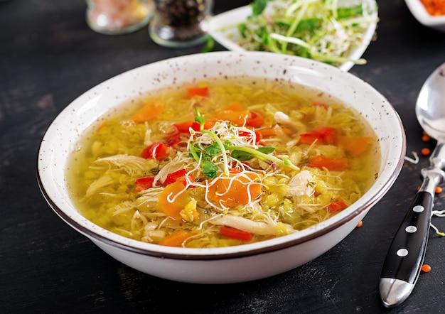 Soep met linzen, wortelen, kippenvlees, paprika, bleekselderij in een kom.