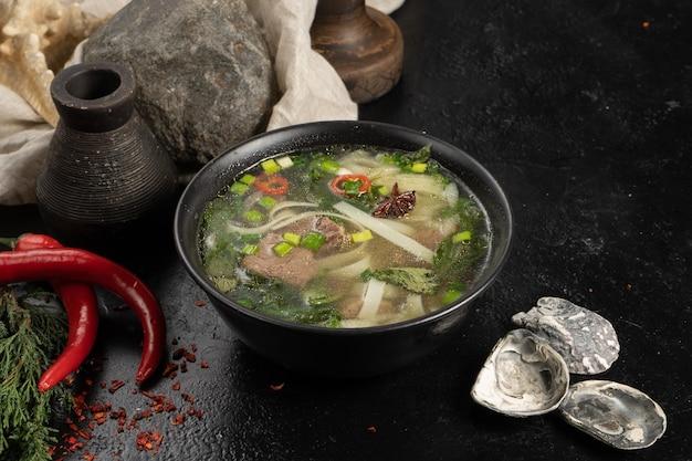 Soep met rundvlees, noedels en groenten op een donkere stenen keukentafel