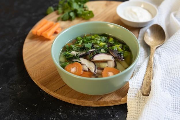 Soep met verse witte champignons en aardappel - traditioneel gerecht uit de russische keuken in een kleikom over donkere houten achtergrond. bovenaanzicht met kopieerruimte.