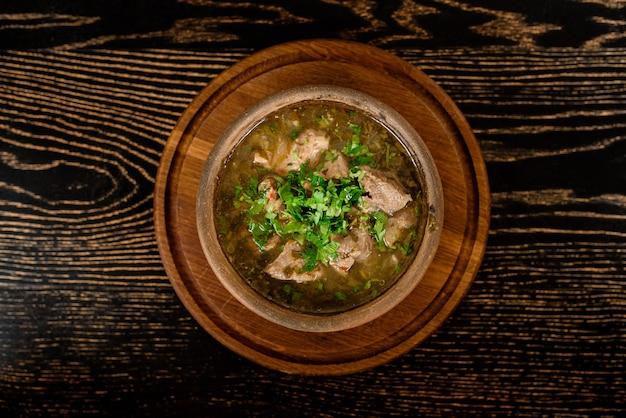 Soep met vlees, zuring en kruiden op een donkere houten tafel. georgische keuken.