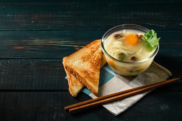 Soep met vleeswortel en pasta in japanse stijl met croutons