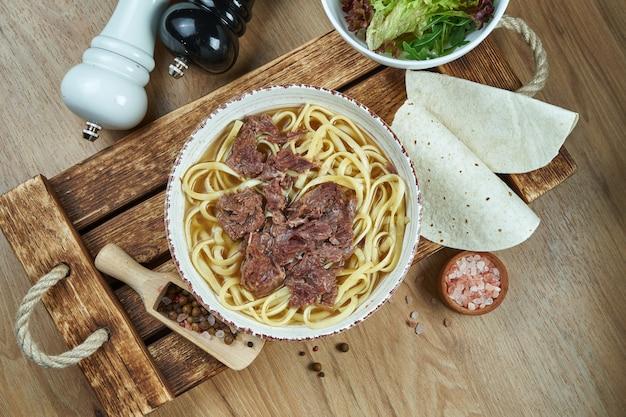 Soep op de bouillon met noedels en gestoofd rundvlees in een witte keramische plaat op een houten dienblad. plat eten