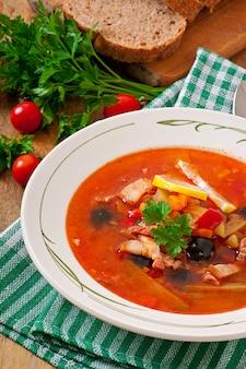 Soep solyanka rus met vlees, olijven en augurken in houten kom