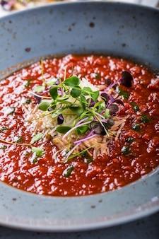 Soep. tomatensoep. italiaanse tomatensoep. mediterrane tomatensoep. italiaanse keuken. mediterraans eten. tomatensoep met kaas en microkruidendecoratie. serveren van tomatensoep op een lepel