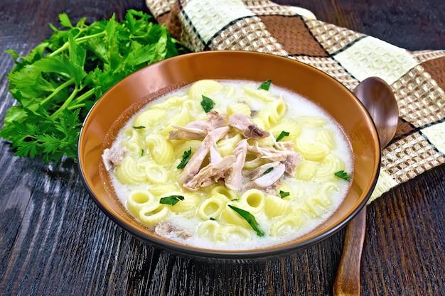 Soep van kippenvlees, pasta met room en koriander in een kleiplaat, servet, peterselie, lepel op een houten plankachtergrond