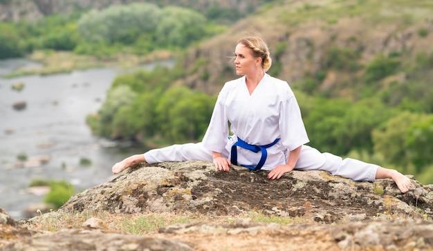 Soepele atletische jonge vrouw die buiten de splitsingen over een rots doet