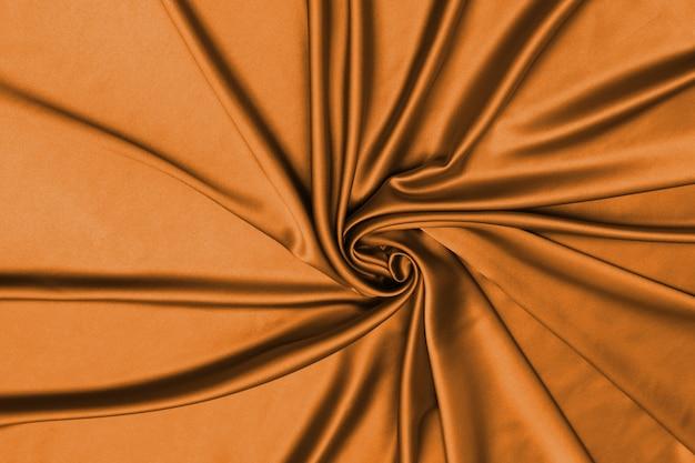 Soepele elegante oranje zijde of satijn luxe doek textuur kan gebruiken als abstracte achtergrond.