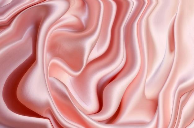 Soepele elegante roze zijde of satijn textuur kan als bruiloft achtergrond worden gebruikt. luxueus ontwerp als achtergrond