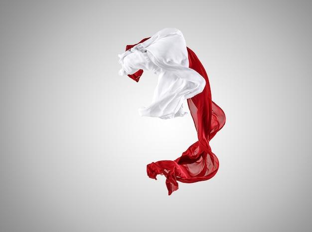 Soepele elegante transparante rode en witte doek gescheiden op een grijze achtergrond.