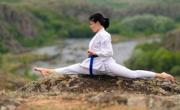 Soepele jonge vrouw in tuniek, broek en vechtsportriem die de splitsingen doet