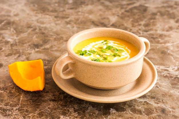 Soeppuree van rijpe pompoen in een kom voor soep op een marmeren achtergrond.