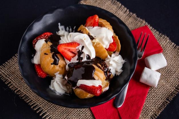 Soesjes met ijs, aardbeien en warme chocolademelk op een zwarte plaat