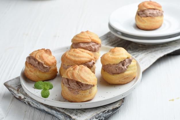 Soezendeeg of slagroomsoesjes gevuld met chocolade vla witte achtergrond