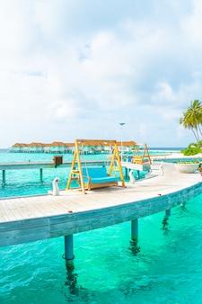 Sofa schommel met tropische maldiven resort en de zee