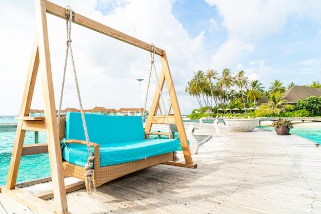 Sofa schommel met tropische maldiven resort en zee achtergrond Premium Foto