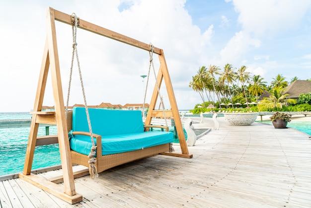 Sofa schommel met tropische maldiven resort en zee achtergrond