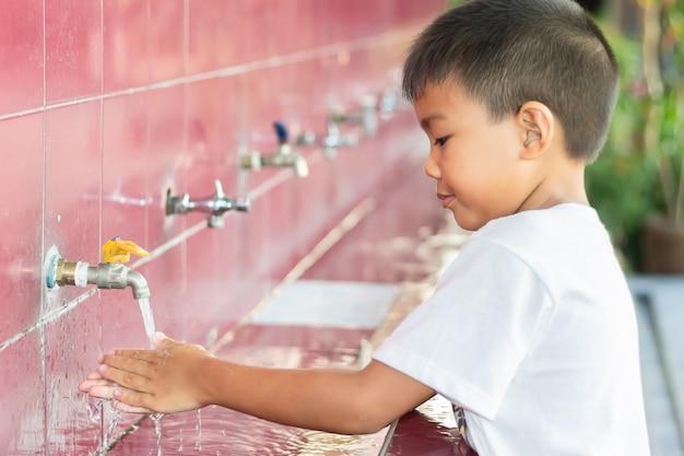 Soft focus, gezondheidszorg en kind concept. aziatische kindjongen die zijn handen wast.