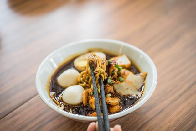 Soft focus hand met chinese eetstokjes eten noodle, een beroemde maleisië loh mee