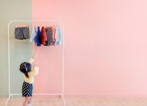 Soft focus of happy kids haar handen wijzen naar stoffen rack voor het kiezen van eigen jurken