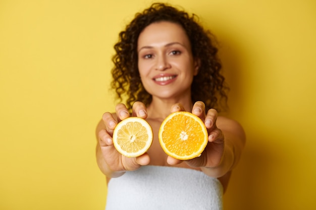 Soft focus op plakjes citrus, citroen en sinaasappel, in de handen van een wazig lachende vrouw van gemengd ras en krullend haar, geïsoleerd