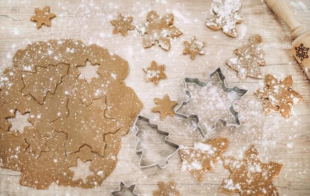 Softfocusdeeg ligt op een houten tafel met bloem en messen. peperkoekkoekjes koken. kerstvoorbereidingen. bovenaanzicht