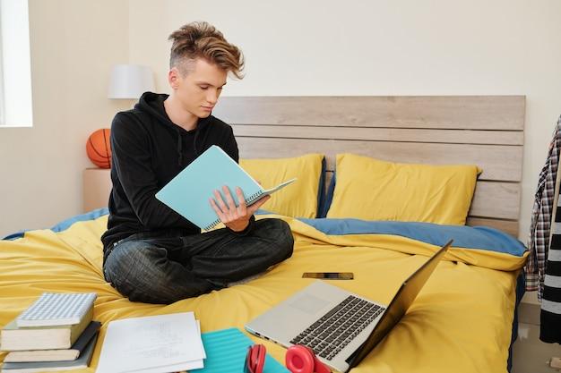 Software engineering student zittend op bed met boeken, laptop en leerboeken rond en schrijven in notitieblok