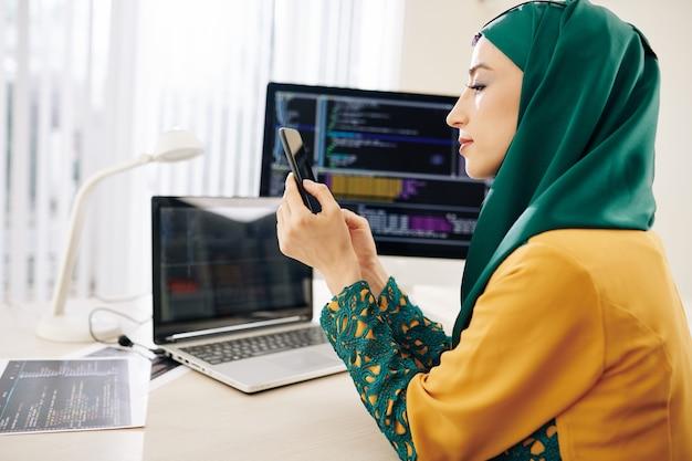 Softwareontwikkelaar die telefoon controleert