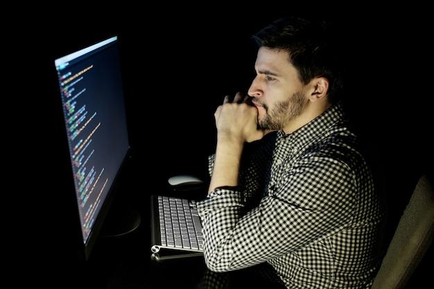 Softwareontwikkelaarcomputer op donker huiskantoor