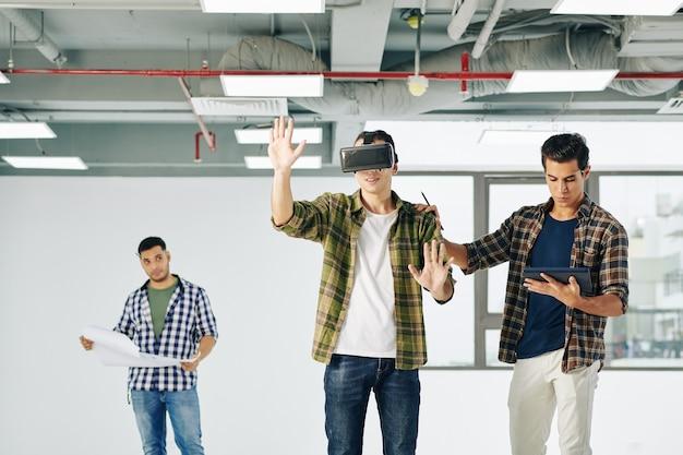 Softwareontwikkelaars die virtual reality-toepassing testen wanneer ingenieur de blauwdruk op de achtergrond controleert