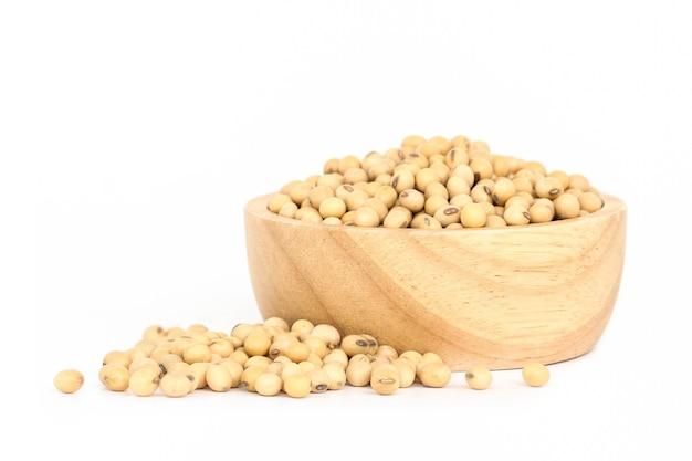 Sojabonen in houten die kom op witte achtergrond wordt geïsoleerd.
