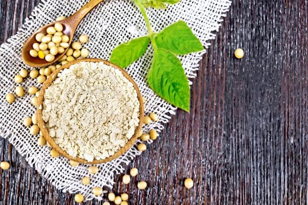 Sojameel in de kom, sojabonen in een lepel en op een servet van jute plundering, groen blad op de achtergrond van een houten plank bovenop