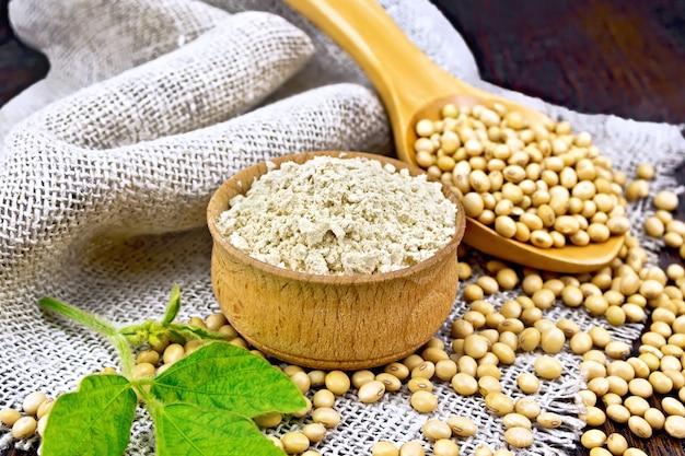 Sojameel in de kom, sojabonen in een lepel en op zak, groen sojablad op een houten plankachtergrond