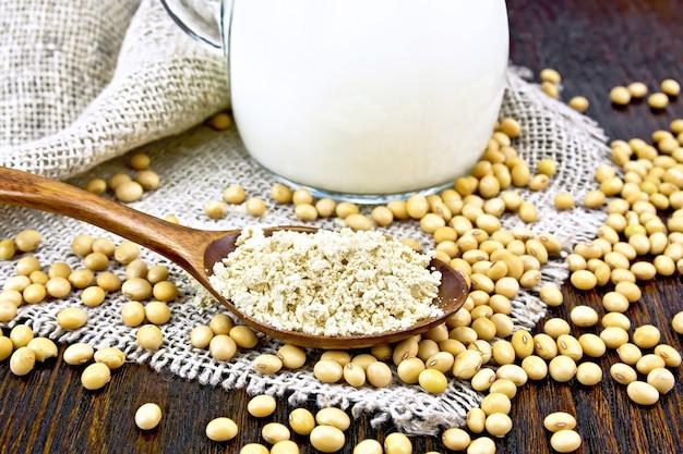 Sojameel in een lepel en melk in een glazen kan, sojabonen op servet van jute op houten plankachtergrond