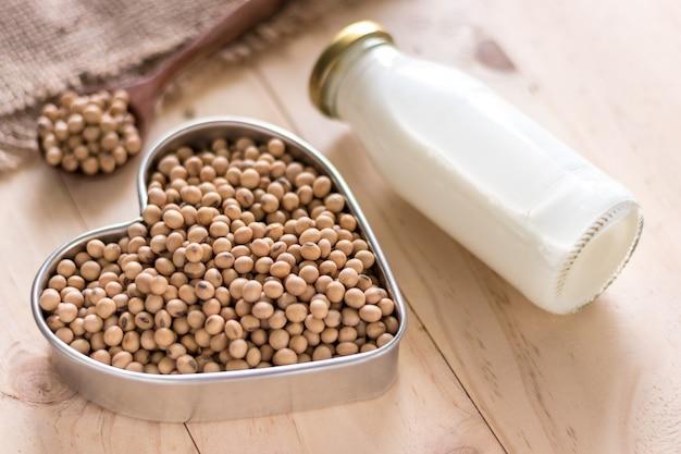 Sojamelk en sojaboon op houten achtergrond, alternatime bron van proteïne voor vagetarian